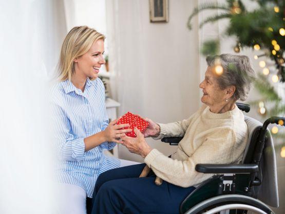 Une femme donne un cadeau à une dame âgée
